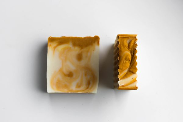 2 soaps white with mustard colored swirls. One standing upright on the right and one laying flat on the left
