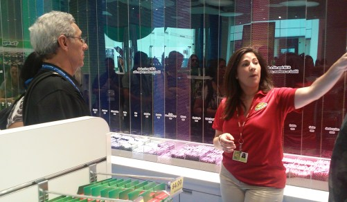 Jackie Vasquez, marketing and sales manager for the soon-to-open Crayola Experience at the Florida Mall, gestures toward another part of the facility's already open gift shop as she explains details of the new attraction to a group of journalists attending ipw.
