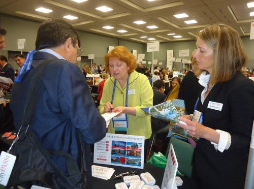 Andrews Cibortti (left), a Brazilian journalist based in Miami, gets top-flight help at the CityPASS table during the Media Marketplace from Megan Allen, president and CEO of CityPASS, and Deborah Wakefield, the company's vice president of communications and public relations.