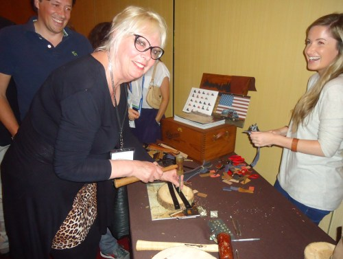 Sylvia Zegfeld, general manager, americanvacations, at the Travel Oregon party making a leather bracelet using hand tools at a table sponsored by Oregon-based Danner Boots.