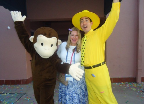 It is hard to tell whether the smile of Angie Zok, Brand USA marketing executive from Miles, is one that is nervous or happy as she is flanked by Curious George and the Man with a Yellow Hat.