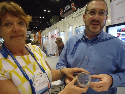 Sally Davis Berry (left), leisure tourism sales and marketing manager for the Corning Museum of Glass, shows off a glass with the sand-blasted NAJ logo, made at the museum, to her colleague, Chris Guidone, director of Wine, Water and Wonders of Upstate New York.