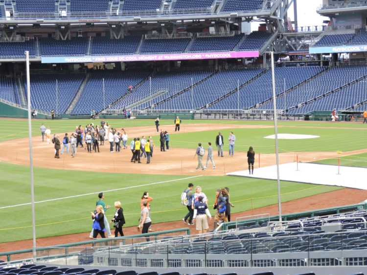 IPW delegates/baseball fans enjoying just milling around on the baseball playing field.