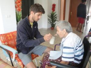 Giovane aiuta un anziano assistendolo durante la colazione