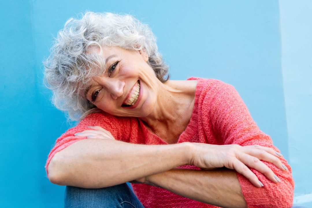 Close up of smiling older woman by blue wall