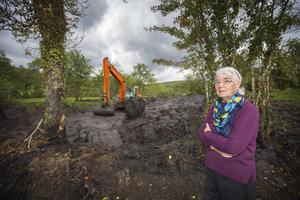 Mary McVeigh (right) on her farm as council workers clear some of the landslide. Photo Brian Farrell