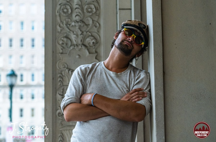 Image of singer/songwriter Ali Awan wearing rainbow sunglasses and a hat