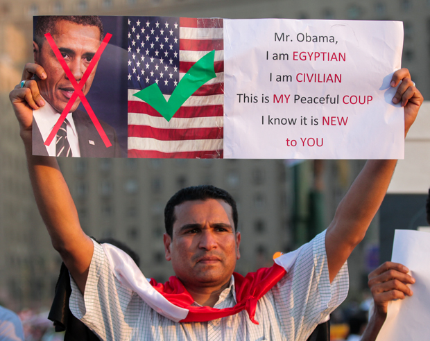 An Egyptian protestor holds a sign showing the anger of some Egyptian people towards the American government. (Photo: Amr Abdel-Hadi / Demotix)