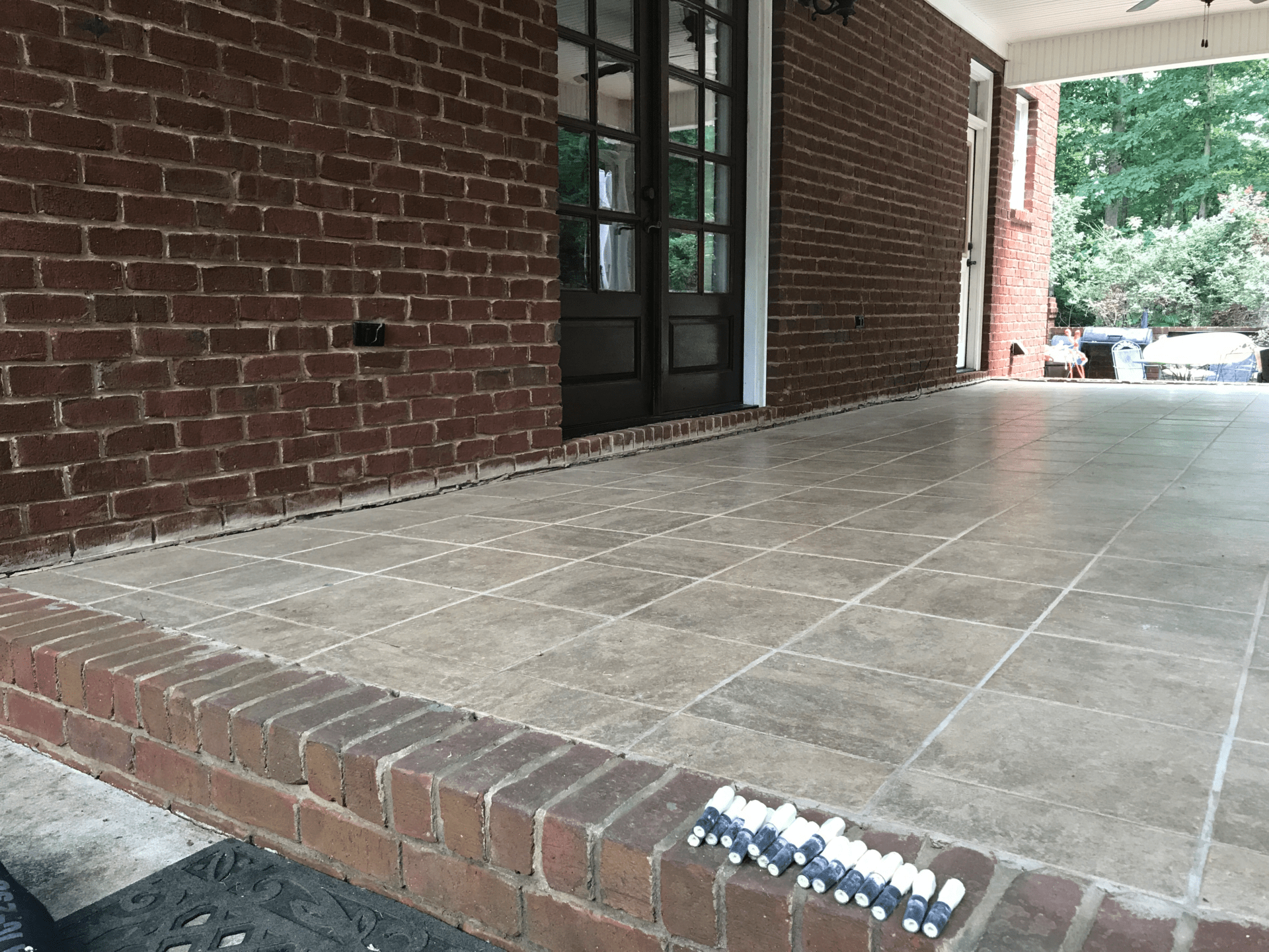 Sinking concrete patio with tile and brick before