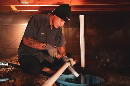 Crew in crawl space installing sump pump