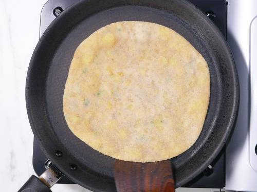 cooking stuffed paratha on a pan