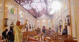 Crime scene officials inspect the site of a bomb blast inside a church in Negombo