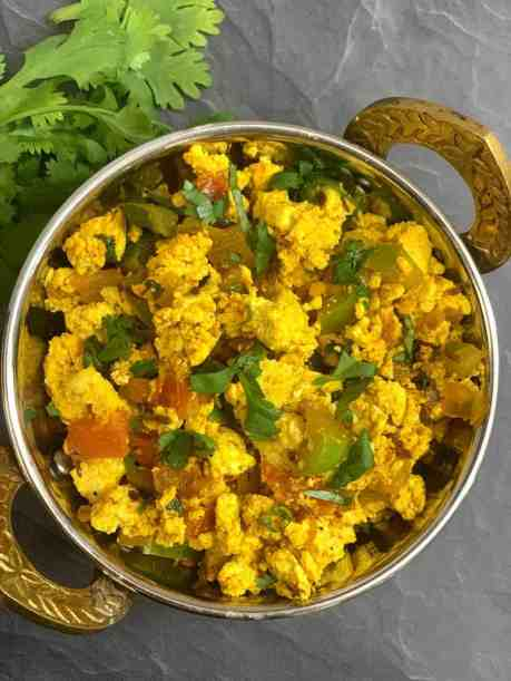 Tofu Bhurji served in a copper bottom serving bowl with coriander on side