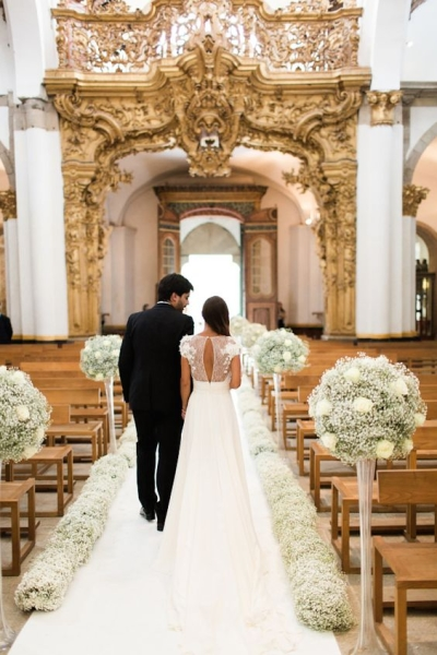 A white wedding aisle runner with bouquets of babybreath - aisle decoration ideas