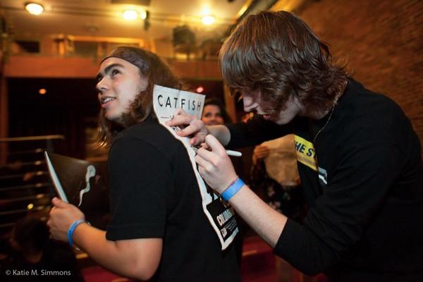 Van signe un autographe sur le dos de son technicien de scène, Larry