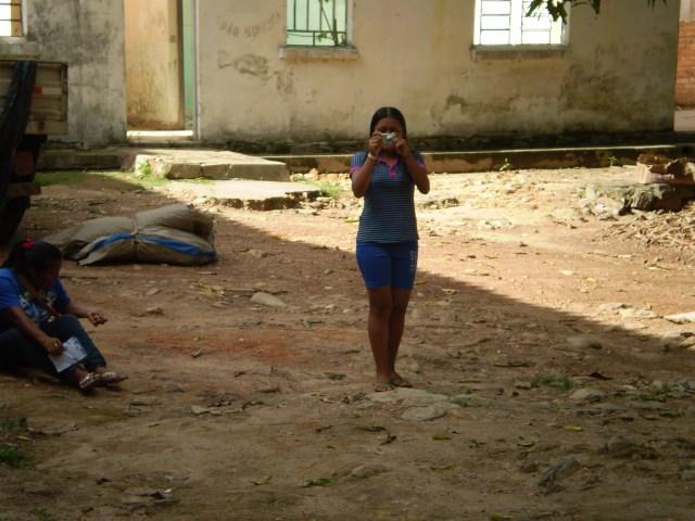 A Aluna de Gestão Territorial Indigena da UFRR, fotografando outros alunos em conversa com o coordenador do Centro de Formação e Cultura Raposa Serra do Sol