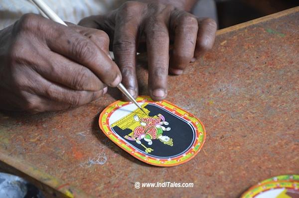 कलाकार गंजिफा को रूप देते हुए