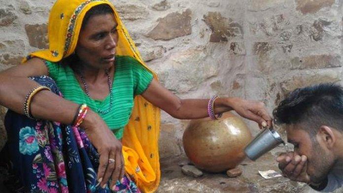 यात्रियों को पानी पिलाती महिला