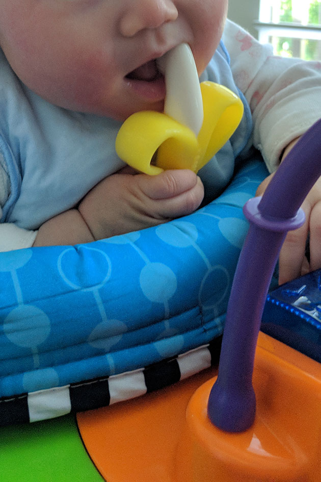 Baby holding onto a banana shaped toothbrush and chewing it.