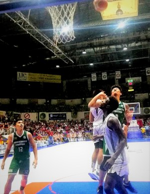 UV veteran forward Monic Soliva (green jersey) attempted to score over Lamine Thiam of SWU in this bit of action in the Game 1 of the CESAFI 2019 Collegiate Basketball Championship game at the Cebu Coliseum.jpg