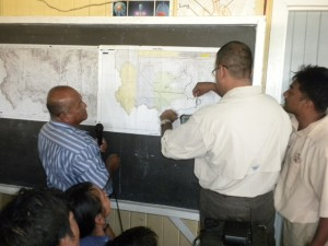 Min. Persaud looking at a map showing the locations in central Baramita where applications have been made for Prospecting Licences