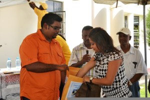 A resident pulling her lot number from the envelope held by Minister of Housing and Water Irfaan Ali at the One Stop Shop at Anna Regina