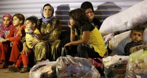 Syrian refugees stand sit in front of a closed shop in Reyhanli, Turkey, Saturday, Aug. 31, 2013.  U.S. President Barack Obama said he has decided that the United States should take military action against Syria in response to a deadly chemical weapons attack, but he said he will seek congressional authorization for the use of force. (AP Photo/Gregorio Borgia)