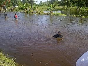 Farmers and workmen in the high water trying to seal the breach [Guyana Times Photo]
