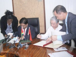 Minister Ashni Singh (left) and China's Ambassador to Guyana Zhang Limin sign the agreements.
