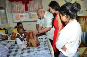 President Donald Ramotar handing over a present to a patient at the Pediatric Ward.