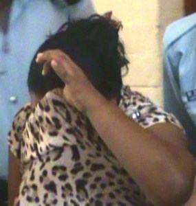 Bibi Ameena Hamza hides her face as she exits the Georgetown Magistrate's Court. [iNews' Photo]