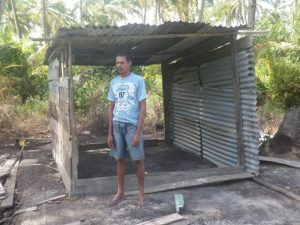 The fisherman standing in front the little shed he erected for shelter on the spot where his house once stood.