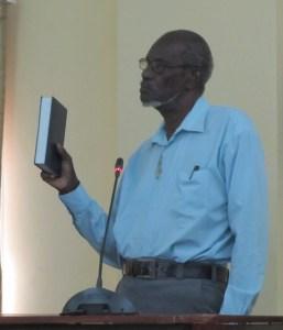 Reverend Rueben Gilbert takes the oath before his testimony. [iNews' Photo]