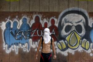 An anti-government protester stands near graffiti during riots in Caracas