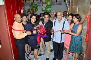 President Donald Ramotar assists in cutting the ribbon to officially open Sueria Manufacturing Inc.  Also in photo are Joint CEOs of the company, Teshawna Lall and Frank Sanichara, baby Sueria, First Lady Deolatchmee Ramotar and Kaieteur News' Publisher Glen Lall