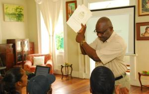 Former Police Commissioner holding up copy of the Guyana Constitution for participants