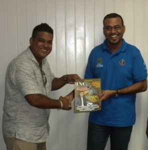 Proprietor of Guyana Inc., Magazine Frank Sanichara hands over the publication to Minister of Natural Resources and the Environment, Robert Persaud. [GINA Photo]