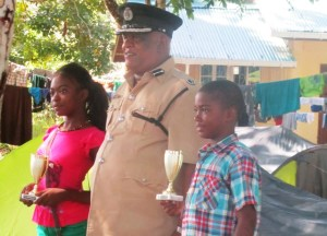 Assistant Commissioner Balram Persaud pose with the best male and female campers. [iNews' Photo]
