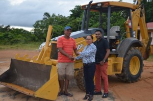 The keys to the back- hoe are handed over to a village councillor by Minister of Amerindian Affairs Pauline Sukhai