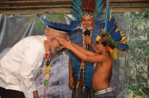 This young Amerindian from Massakenari places a chief's headdress on President Ramotar. [GINA Photo]