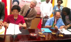 China's Health Minister, Li Bin and Guyana's Health Minister, Dr Bheri Ramsaran sign the MOU for the Medical House of Science. [GINA Photo]