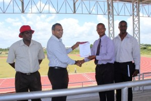 Minister of Sport, Dr Frank Anthony (second left) and Aubrey Hutson (second right) share a moment with the certification of the track in the presence of  Deputy Permanent Secretary of the Ministry of Sport Steve Ninvalle (extreme left) and Permanent Secretary of the Ministry of Sport, Alfred King (extreme right). [iNews' Photo]