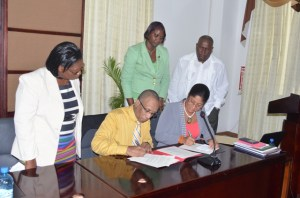 Keith Burrowes, Chief Executive Officer, Guyana Office for Investment and Madaline Headley-Woodroffe, Business Development Officer, Barbados Industrial Development Corporation sign the Memorandum of Understanding to establish Trade Missions between Guyana and Barbados. [GINA Photo]