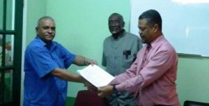 Agreement handed over to Mr. Charles Ogle, the Chief Labour Occupational Safety and Health Officer by Mr. Omadat Samaroo, Chief Executive Officer of BBCI.