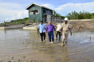 President Ramotar, and Public Works Minister, Robeson Benn head towards another East Coast village after checking out the pump station at Paradise. [GINA Photo]