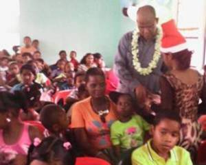 PPP General Secretary Clement Rohee distributing gifts to the Children with assistance from local comrades.