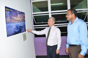 """Minister of Culture, Youth and Sport, Dr. Frank Anthony and China's Ambassador to Guyana, Zhang Limin viewing the exhibits at the """"Chinese Dream"""" photographic Exhibition at the Guyana National Museum."""