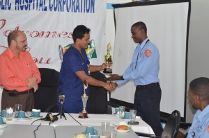 Georgetown Public Hospital Corporation's Director of Accident and Emergency Department, Dr. Zulfikar Bux handing over the trophy for best performing Emergency Medical Technician in 2014 to Ron Morris.