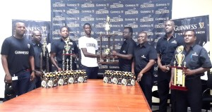 The winning trophies on display as officials of Banks DIH and the West Demerara organisers pose for the cameras. [iNews' Photo]