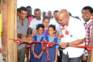 Minister of Local Government & Regional Development , Norman Whittaker along with beneficiaries, and officials cutting the ribbon to commission the Friendship swine  facility.